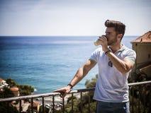 Hombre hermoso que bebe el caf? americano al aire libre imagenes de archivo