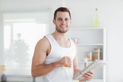 Hombre hermoso que bebe el zumo de naranja mientras que lee las noticias Imagenes de archivo
