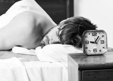 Hombre hermoso que bosteza y que estira sus brazos para arriba Imagen que muestra al hombre joven que estira en cama Divertido ac imágenes de archivo libres de regalías