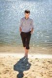 Hombre hermoso que camina en el río del coste Foto de archivo libre de regalías