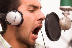 Hombre hermoso que canta en estudio de la música Imagenes de archivo