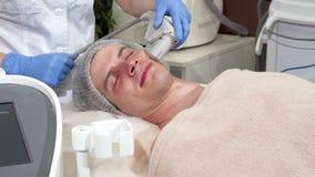 Hombre hermoso que consigue que rejuvenece procedimiento en la clínica de la cosmetología almacen de video