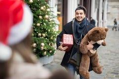 Hombre hermoso que da los presentes para la Navidad a su novia Imagenes de archivo