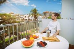 Hombre hermoso que desayuna sano en terraza del hotel fotos de archivo