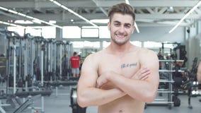 Hombre hermoso que descansa durante un entrenamiento en el gimnasio metrajes