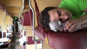 Hombre hermoso que duerme con un oso de peluche del juguete en un tren Sueño cansado del estudiante del trabajador después del tr metrajes
