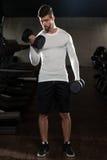 Hombre hermoso que ejercita el bíceps con pesas de gimnasia Foto de archivo