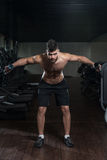 Hombre hermoso que ejercita el hombro con pesas de gimnasia Imagen de archivo libre de regalías