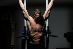 Hombre hermoso que ejercita su ABS en el gimnasio Foto de archivo