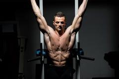 Hombre hermoso que ejercita su ABS en el gimnasio Imagenes de archivo