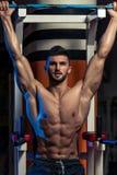 Hombre hermoso que ejercita su ABS en el gimnasio Foto de archivo libre de regalías
