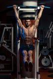 Hombre hermoso que ejercita su ABS en el gimnasio Imágenes de archivo libres de regalías