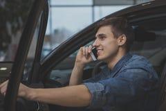 Hombre hermoso que elige el nuevo automóvil para comprar fotografía de archivo libre de regalías