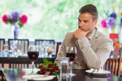 Hombre hermoso que espera a su novia en el restaurante Fotos de archivo