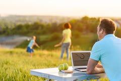 Hombre hermoso que goza del ordenador portátil al aire libre Fotografía de archivo