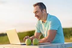 Hombre hermoso que goza del ordenador portátil al aire libre Foto de archivo libre de regalías