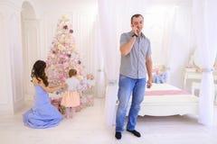 Hombre hermoso que habla en el teléfono en luz del dormitorio en fondo de foto de archivo libre de regalías
