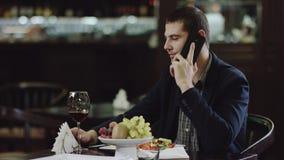 Hombre hermoso que habla en el teléfono móvil en café y vino de consumición metrajes