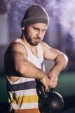 Hombre hermoso que hace ejercicio con pesas de gimnasia foto de archivo