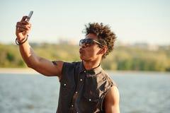 Hombre hermoso que hace el selfie y que hace muecas con la boca abierta Imagen de archivo