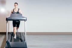Hombre hermoso que hace los ejercicios cardiios, corriendo en las ruedas de ardilla en el gimnasio Fotografía de archivo