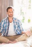 Hombre hermoso que hace yoga en su cama Foto de archivo