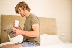 Hombre hermoso que lee las noticias y que bebe el café Foto de archivo