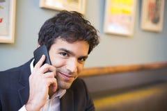 Hombre hermoso que llama con un teléfono celular en la barra de café, mirando el Ca fotografía de archivo