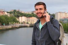 Hombre hermoso que llama por el teléfono del puerto con el espacio de la copia Imagenes de archivo