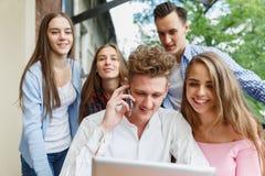 Hombre hermoso que llama un teléfono Grupo de adolescencias emocionadas con un móvil en un fondo del café Nuevo concepto del smar Fotografía de archivo libre de regalías