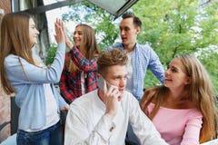 Hombre hermoso que llama un teléfono Grupo de adolescencias emocionadas con un móvil en un fondo del café Nuevo concepto del smar Imagen de archivo libre de regalías