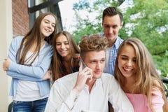 Hombre hermoso que llama un teléfono Grupo de adolescencias emocionadas con un móvil en un fondo del café Nuevo concepto del smar Fotos de archivo