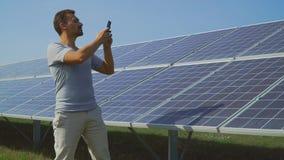 Hombre hermoso que lleva a cabo los expedientes de los paneles solares metrajes