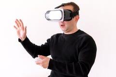 Hombre hermoso que lleva y que juega realidad virtual en fondo blanco aislado Acción del muchacho en casco de la realidad virtual Fotografía de archivo