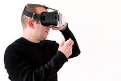 Hombre hermoso que lleva y que juega realidad virtual en fondo blanco aislado Acción del muchacho en casco de la realidad virtual Imágenes de archivo libres de regalías