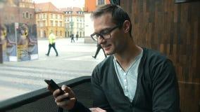 Hombre hermoso que manda un SMS en el teléfono móvil que se sienta por un café de la ventana en una ciudad almacen de video