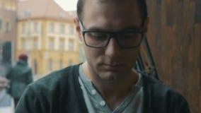 Hombre hermoso que manda un SMS en el teléfono móvil que se sienta por un café de la ventana en una ciudad metrajes