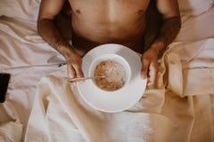 Hombre hermoso que miente en cama con el desayuno sano por la mañana Individuo atractivo que sonríe en dormitorio en casa, jóvene fotos de archivo