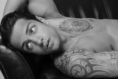 hombre hermoso que miente en un sofá foto de archivo