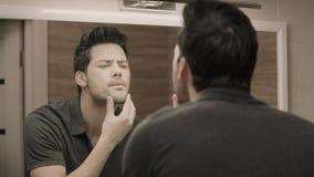 Hombre hermoso que mira la cara delante del espejo Individuo del primer que ajusta la camiseta metrajes