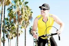 Hombre hermoso que monta su bicicleta Foto de archivo