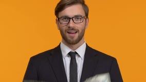 Hombre hermoso que muestra las manos completas de los dólares, salarios decentes, inversión, primer almacen de metraje de vídeo