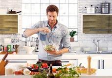 Hombre hermoso que prepara la ensalada en cocina Foto de archivo