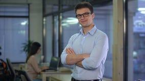 Hombre hermoso que presenta en el fondo de la oficina, wageworker, empleo oficial metrajes