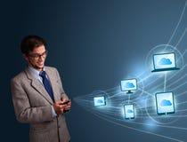 Hombre hermoso que pulsa en smartphone con la computación de la nube Foto de archivo libre de regalías