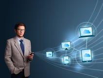 Hombre hermoso que pulsa en smartphone con la computación de la nube fotos de archivo libres de regalías