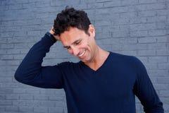 Hombre hermoso que ríe con la mano en pelo contra la pared gris Fotos de archivo