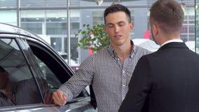 Hombre hermoso que sacude las manos con el vendedor de coches en la representación del automóvil almacen de metraje de vídeo