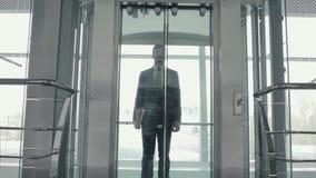 Hombre hermoso que sale del elevador en el aeropuerto almacen de metraje de vídeo