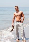 Hombre hermoso que se coloca en la playa Imagen de archivo